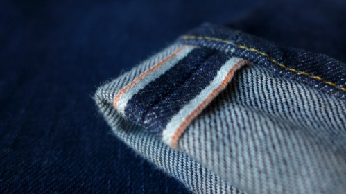 The beautiful 13 oz. selvedge denim edged in burnt orange